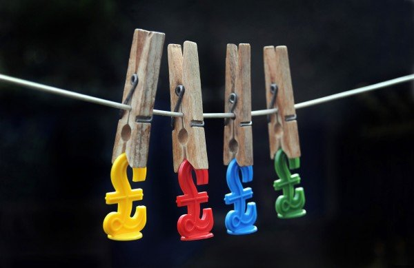 BRITISH POUND SIGNS HANGING ON FROM PEGS ON DOMESTIC WASHING LINE RE THE ECONOMY BANKS INTEREST RATES MORTGAGES INCOME CASH UK