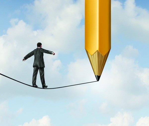 Risk planning and leadership solutions with a businessman walking on a dangerous tight rope with a pencil drawing the future pat