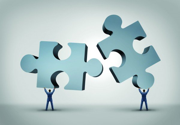 Teamwork and leadership business concept with two giant three dimensional puzzle pieces coming together from a partnership agree